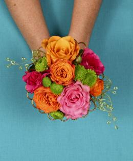 This fun and colorful hand held bouquet features orange, pink & green flowers with fun accents of wire.